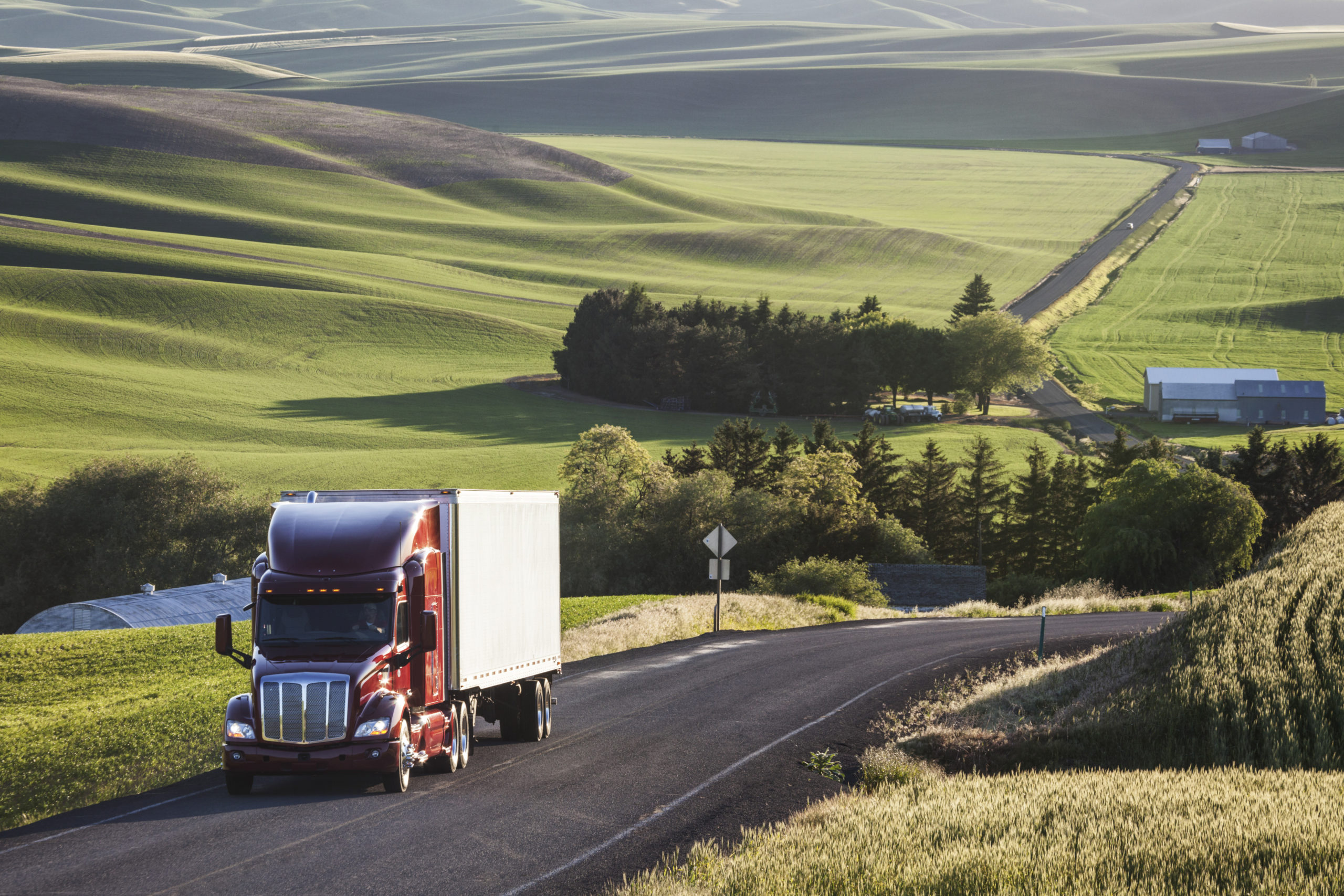 commercial truck driving though wheat fields of ea RSNKYQG scaled